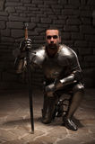 Medieval knight kneeling with sword Royalty Free Stock Image