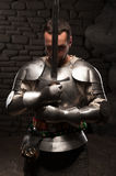 Medieval knight kneeling with sword. Waistup portrait of medieval knight keeping sword on chest on a dark stonewall background Stock Image