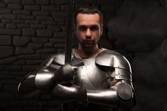 Medieval knight kneeling with sword. Waistup portrait of medieval knight keeping sword on chest on a dark stonewall background Stock Photography