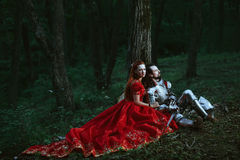 Medieval knight with lady. Medieval knight with his beloved lady in red dress stock photo