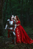 Medieval knight with lady. Medieval knight with his beloved lady in red dress stock photos