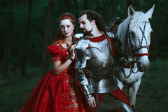 Medieval knight with lady. Medieval knight with his beloved lady in red dress Royalty Free Stock Images