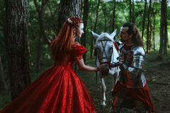 Medieval knight with lady. Medieval knight with his beloved lady in red dress stock images