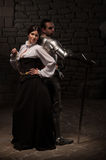 Medieval knight and lady posing. Beautiful couple in historical costumes, medieval knight with sword and lady posing back to back on dark stonewall background Stock Photo