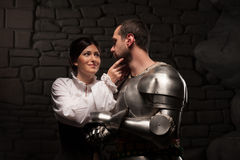 Medieval knight and lady posing. Beautiful couple in historical costumes, medieval knight with sword and lady hugging and petting on dark stonewall background stock images