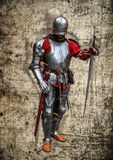 Medieval knight lord poster. Armoured knight with the sword on grunge background Royalty Free Stock Photo