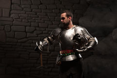 Medieval Knight posing with sword in a dark stone. Background. Waist up portrait Royalty Free Stock Photography