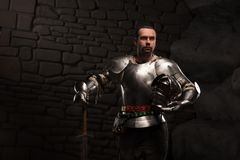 Medieval Knight posing with sword in a dark stone. Background. Waist up portrait Stock Photo