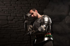 Medieval Knight posing with sword in a dark stone. Background. Waist up portrait Stock Photography