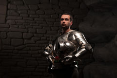 Medieval Knight posing with sword in a dark stone. Background. Waist up portrait Stock Images