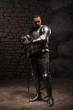 Medieval Knight posing with sword in a dark stone. Medieval Knight posing with sword  and helmet in a dark stone background. Full-length portrait Stock Photo