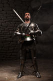 Medieval Knight posing with two swords on in a Royalty Free Stock Photography