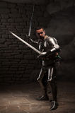 Medieval Knight posing with two swords on in a Stock Photo
