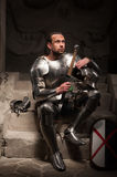 Medieval knight sitting on the steps of ancient Royalty Free Stock Photos