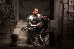 Medieval knight sitting on the steps of ancient. Portrait of medieval knight in armor with shield and sword sitting on steps of ancient temple with skull, dark Royalty Free Stock Images