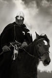 Medieval knight of St. John (Hospitaller). Riding on a bay horse Royalty Free Stock Photography