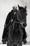 Medieval knight of St. John (Hospitallers). On a bay horse Royalty Free Stock Image