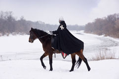 Medieval knight of St. John (Hospitallers). On a bay horse Stock Photos