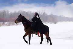 Medieval knight of St. John (Hospitallers). On a bay horse Royalty Free Stock Photo
