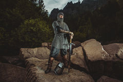 Medieval knight stands on rocks holding a sword Royalty Free Stock Image
