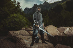 Medieval knight stands on rocks holding a sword Royalty Free Stock Photography