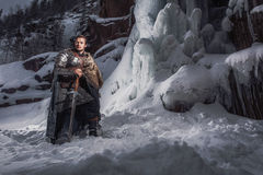 Medieval knight with sword in armor as style Game of Throne. S in Winter Rock Landscapes Royalty Free Stock Images