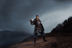 Medieval knight with sword in armor as style Game of Thrones in. Winter Forest Landscapes royalty free stock image