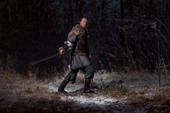 Medieval knight with sword in armor as style Game of Thrones in. Winter Forest Landscapes Stock Photography