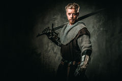 Medieval knight with sword and armour. Young medieval knight posing on dark background Royalty Free Stock Images