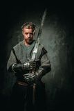 Medieval knight with sword and armour. Young medieval knight posing on dark background Stock Image