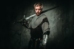 Medieval knight with sword and armour. Young medieval knight posing on dark background royalty free stock photography