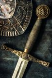 Sword detail over antique background. Medieval knight sword and shield closeup over antique dark background royalty free stock photo