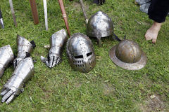 Medieval knights helmets and gloves. Medieval knights helmet with visor outdoors with accessories in the background Stock Image