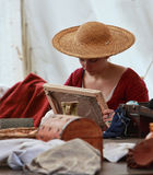 Medieval Lady. Nogent le Rotrou,France, 11.05.2013: Environmental portrait of a young medieval lady weaving under her tent during the Percheval Medieval Festival Royalty Free Stock Image