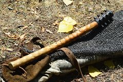 Medieval light mace with blunt spikes placed on chainmail armor and leather gauntlet Stock Photo
