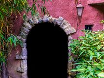 Medieval looking arch doorway with a lantern, castle architecture, dark door opening in a wall