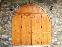 Medieval looking arched top doors set in a stone castle wall