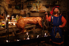 Medieval man doing roasted pig on the rack  in ancient castle kit Royalty Free Stock Photos