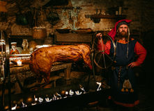 Medieval man doing roasted pig on the rack stock photo