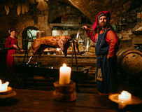 Medieval man doing roasted pig on the rack royalty free stock photos