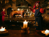 Medieval man doing roasted pig on the rack royalty free stock photography