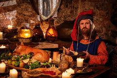 Medieval man eat and drink in ancient castle kitchen interior. stock images
