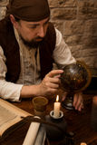 Medieval man pointing at a old globe, concept travelling and tou Stock Photo