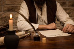 Medieval man sitting on a table with a contract, concept busines Royalty Free Stock Images