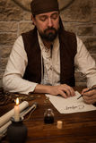Medieval man sitting on a table and sign a contract Stock Images