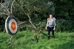 Medieval man stands in the Nature. Arrow, curve and quiver stands besides and target from straw with arrows Royalty Free Stock Photo