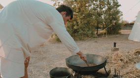 Medieval man stirs the pottage with meat in the cauldron on the fire stock video
