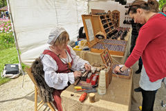 Medieval Market celebration in Cinquantenaire Parc in Brussels, Belgium. BRUSSELS, BELGIUM-MAY 19, 2013: Unidentified artisan artist shows her art during Royalty Free Stock Image