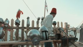 Medieval master rubbing iron armor, helmets and swords stock video footage