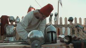 Medieval master rubbing iron armor, helmets and swords stock video